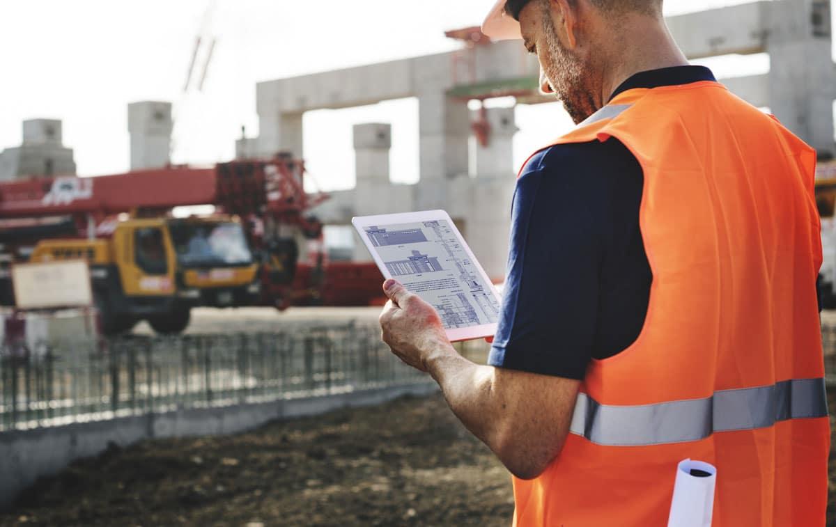 Mitarbeiter auf Baustelle betrachtet Pläne auf Tablet