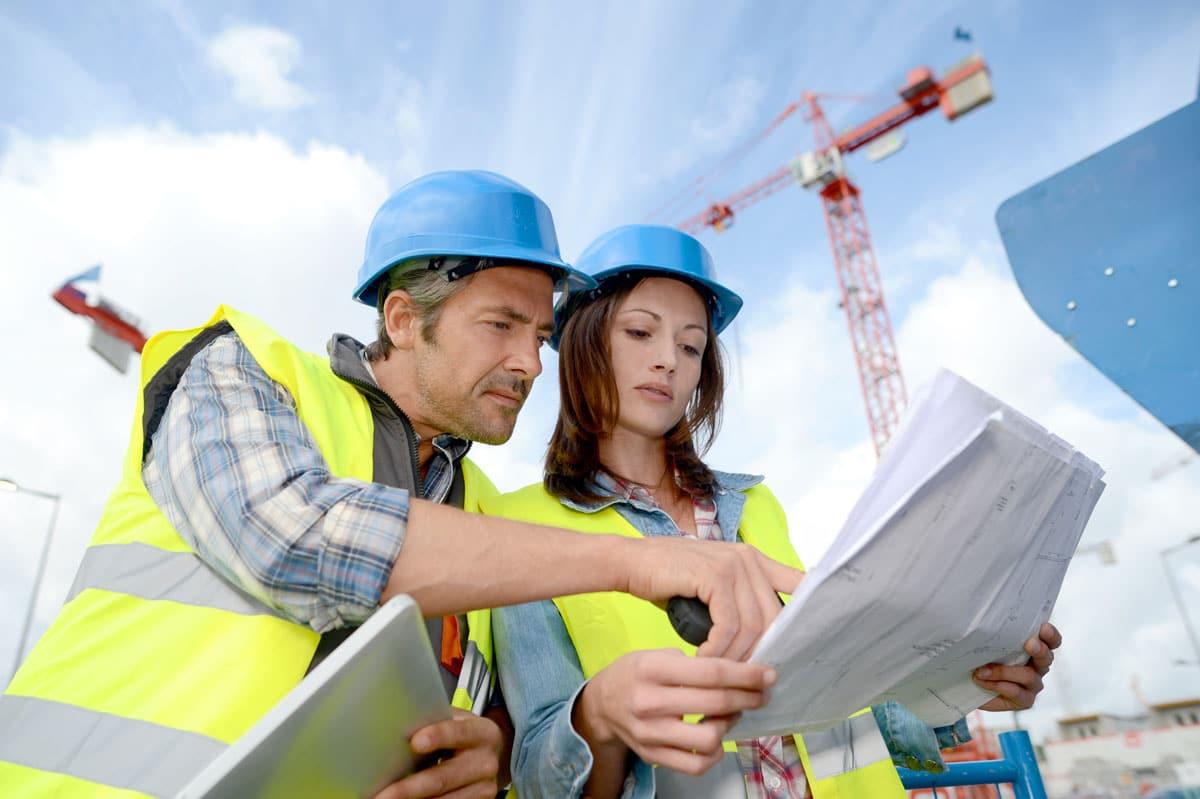 Zwei Mitarbeitende auf Baustelle betrachten Baupläne