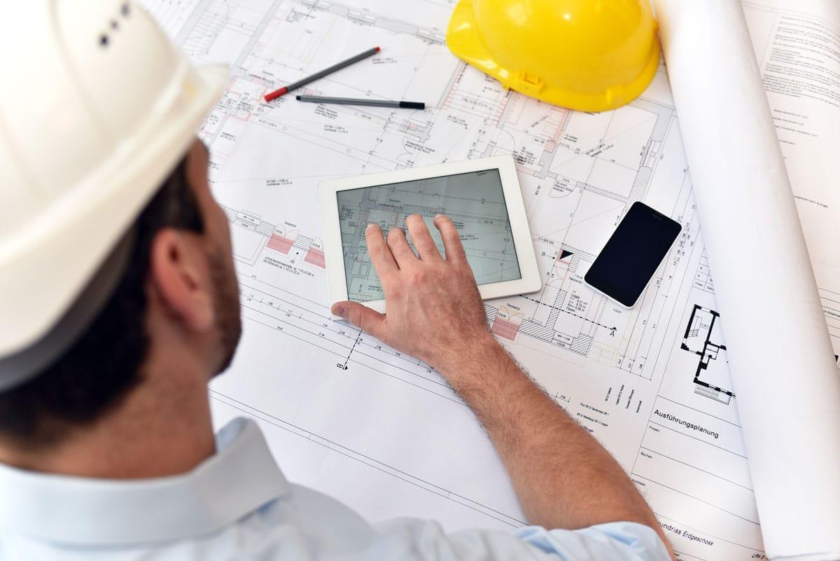 Mitarbeiter auf Baustelle arbeitet mit Bauplänen und Tablet-PC